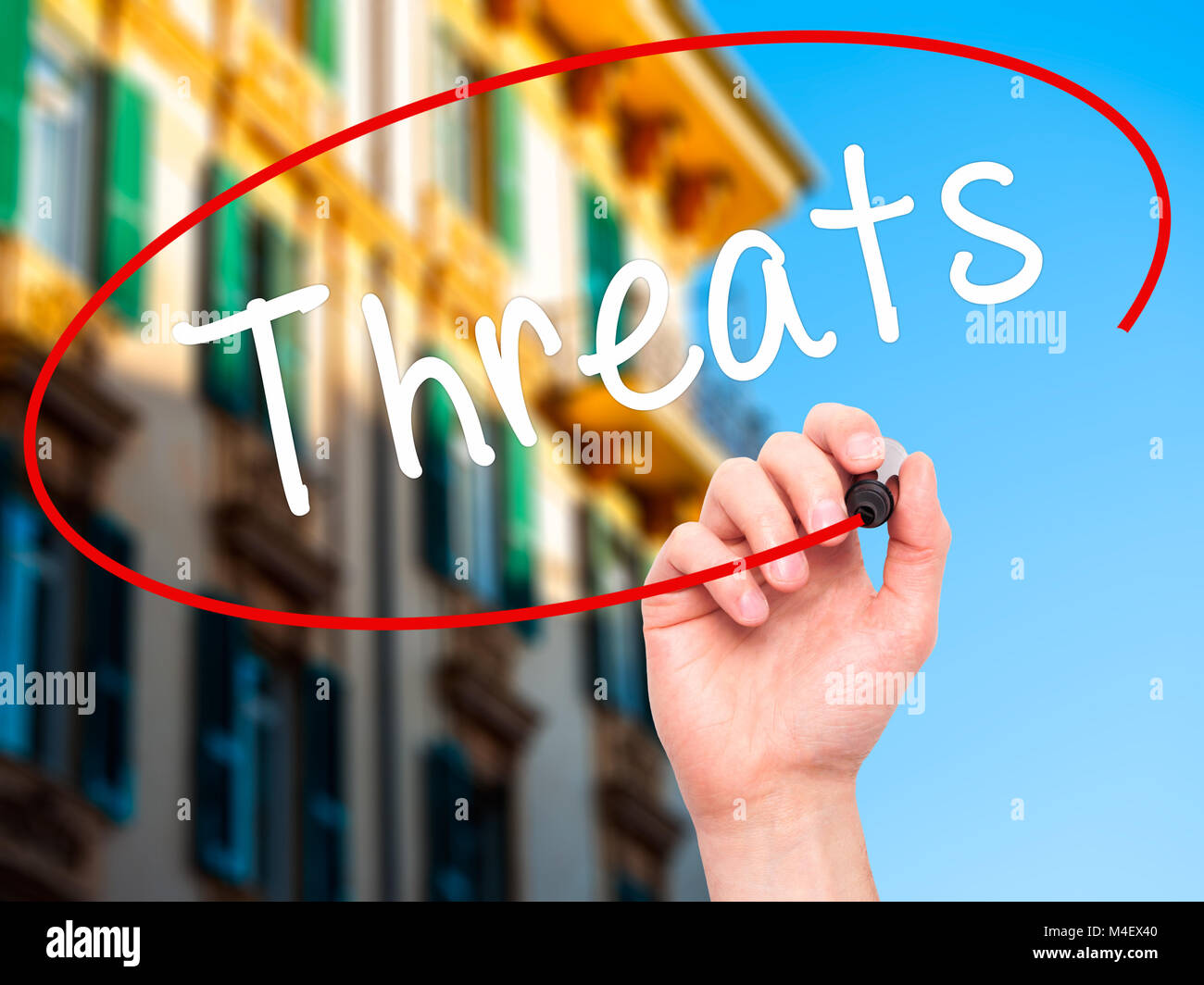 Man Hand writing Threats with black marker on visual screen - Stock Image