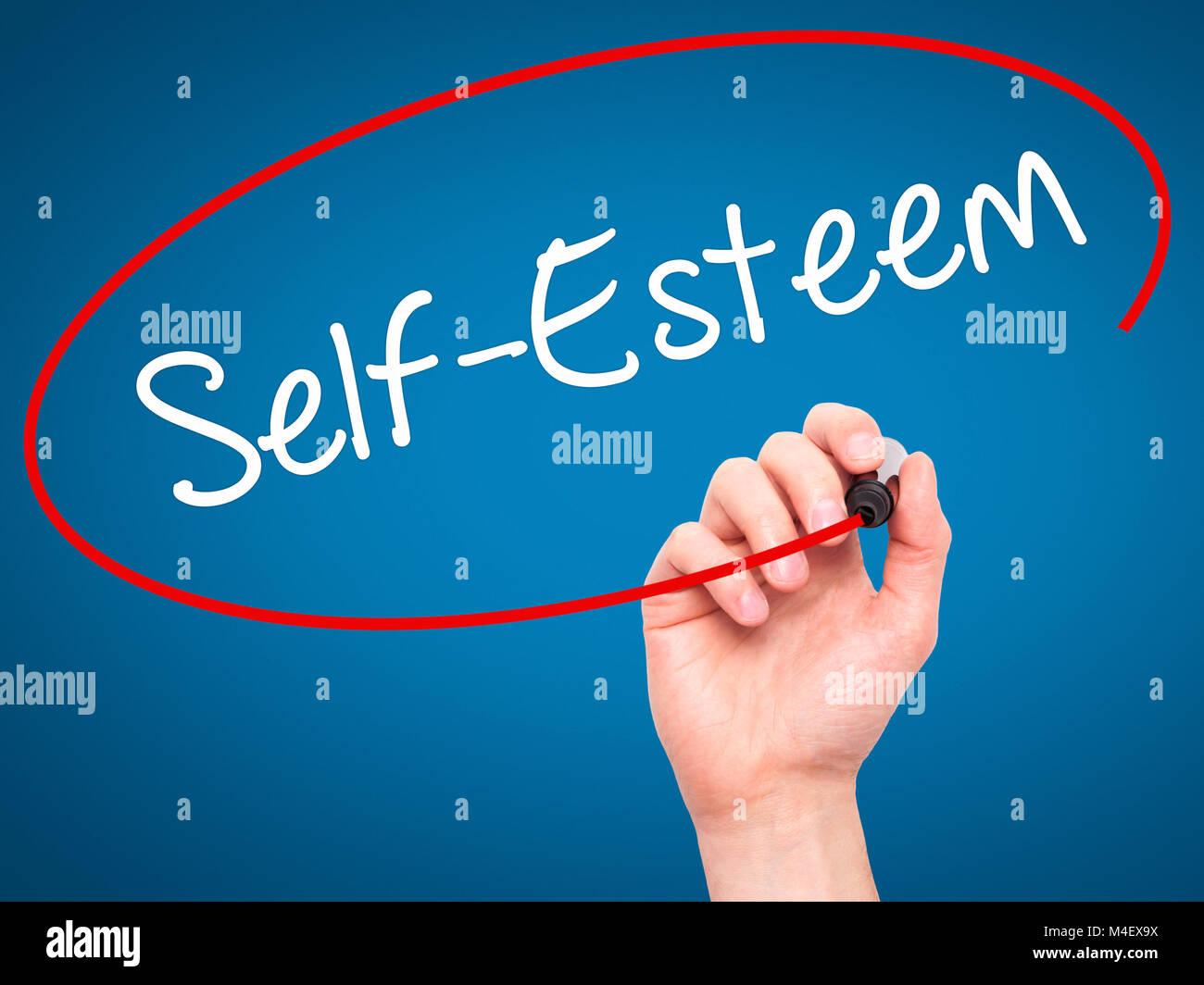 Man Hand writing Self-Esteem with black marker on visual screen. - Stock Image