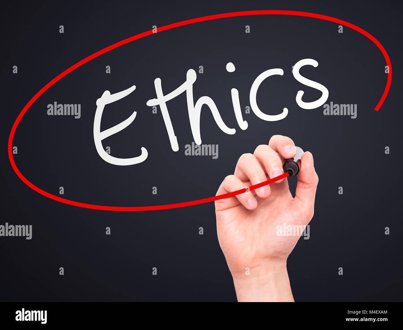 Man hand writing Ethics on visual screen - Stock Image