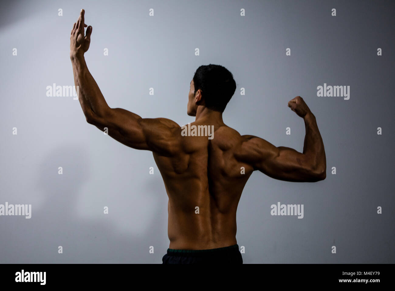 Fitness model displaying his back muscles. Medium shot. Rear View. - Stock Image