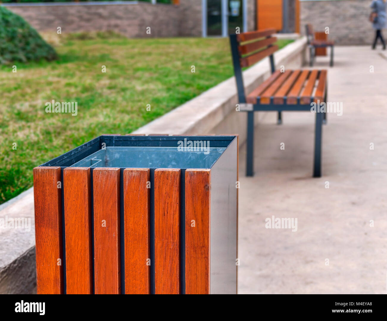 A trash can and a park bench in the urban city block - Stock Image