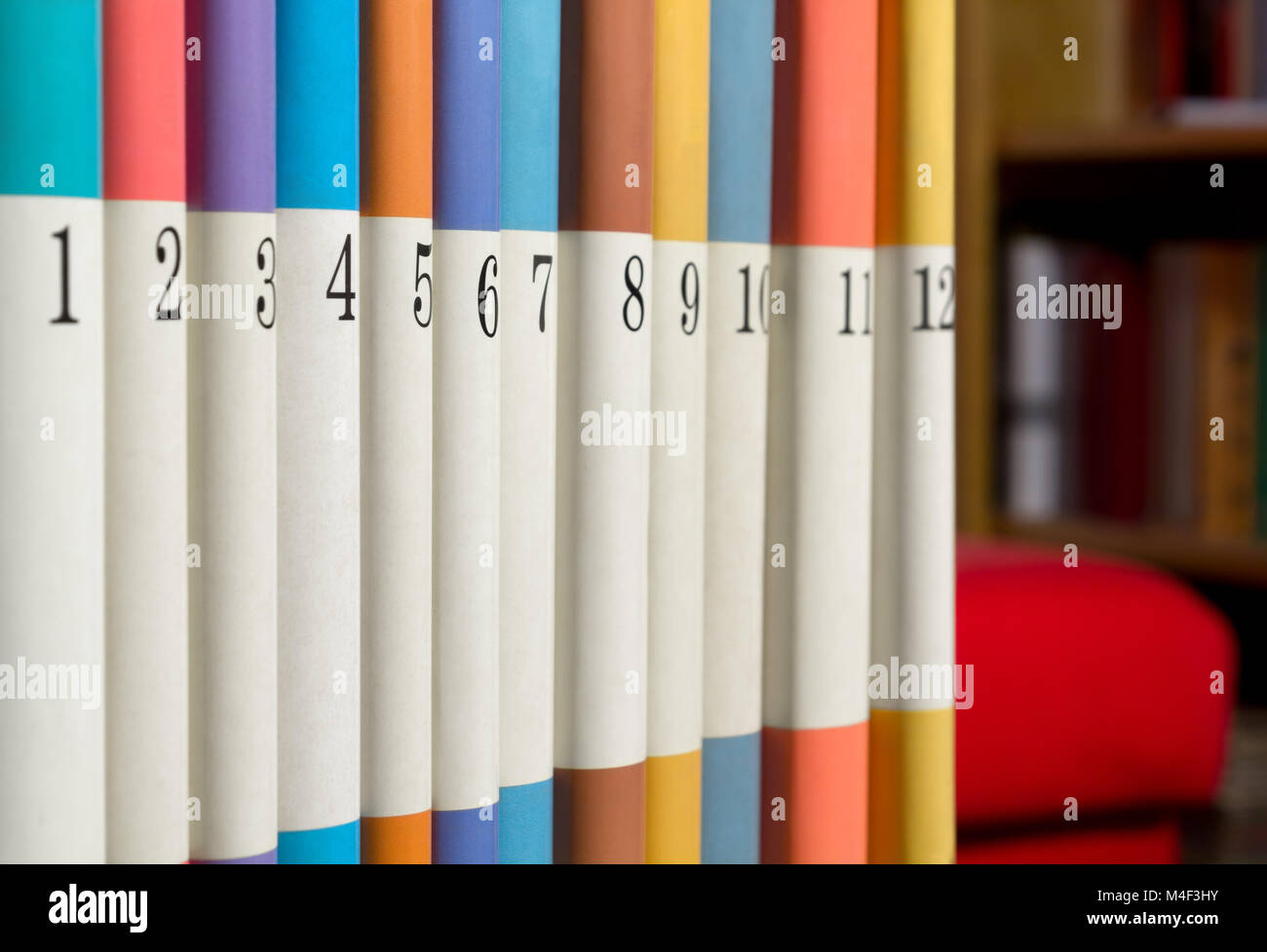 Twelve numbered books in a row with a bookcase and a red sofa in the background - Stock Image
