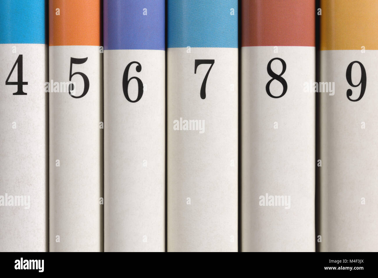 Six colored numbered books in a row - Stock Image