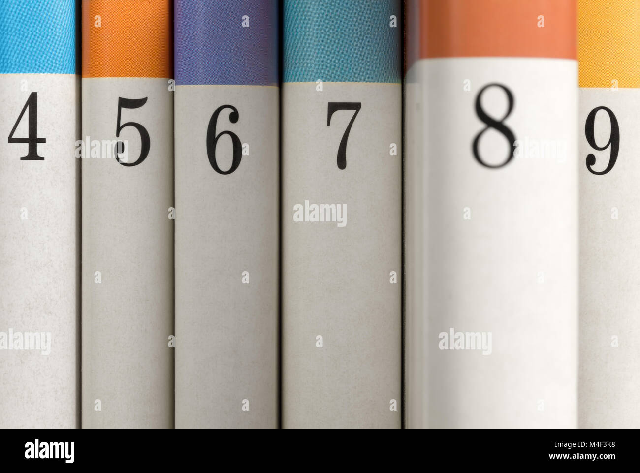 Six colored numbered books with book number eight partially pulled out from the row Stock Photo