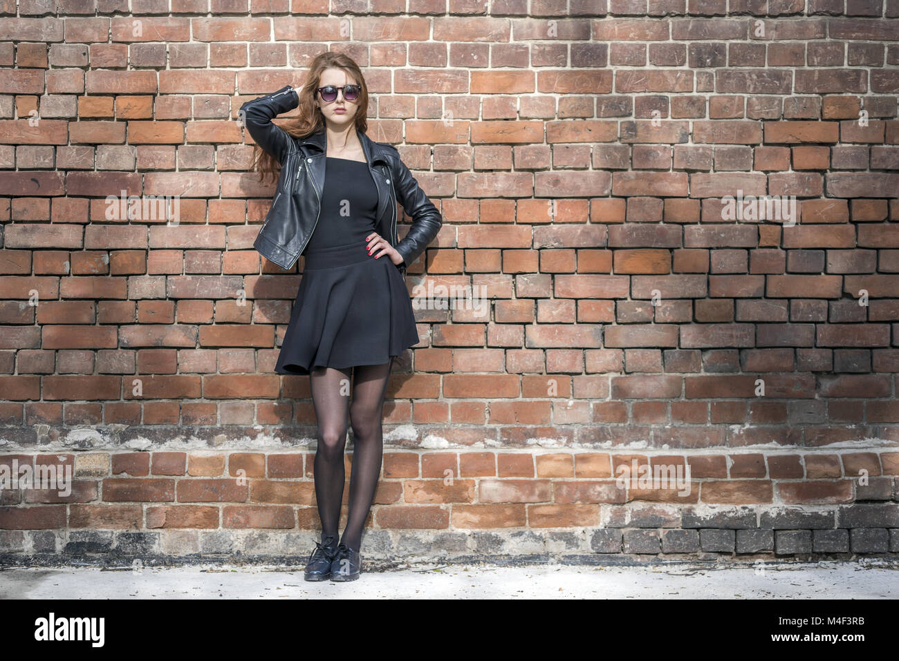 Girl with long hair near an old brick wall - Stock Image