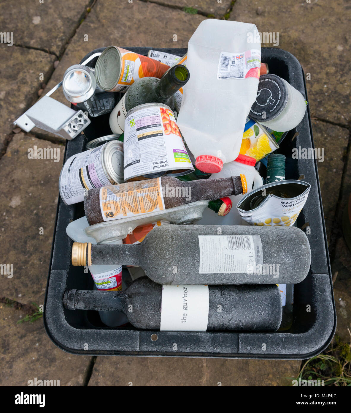 Frost-covered recycling box of glass, plastic and metal awaiting collection outside a Shropshire house. - Stock Image