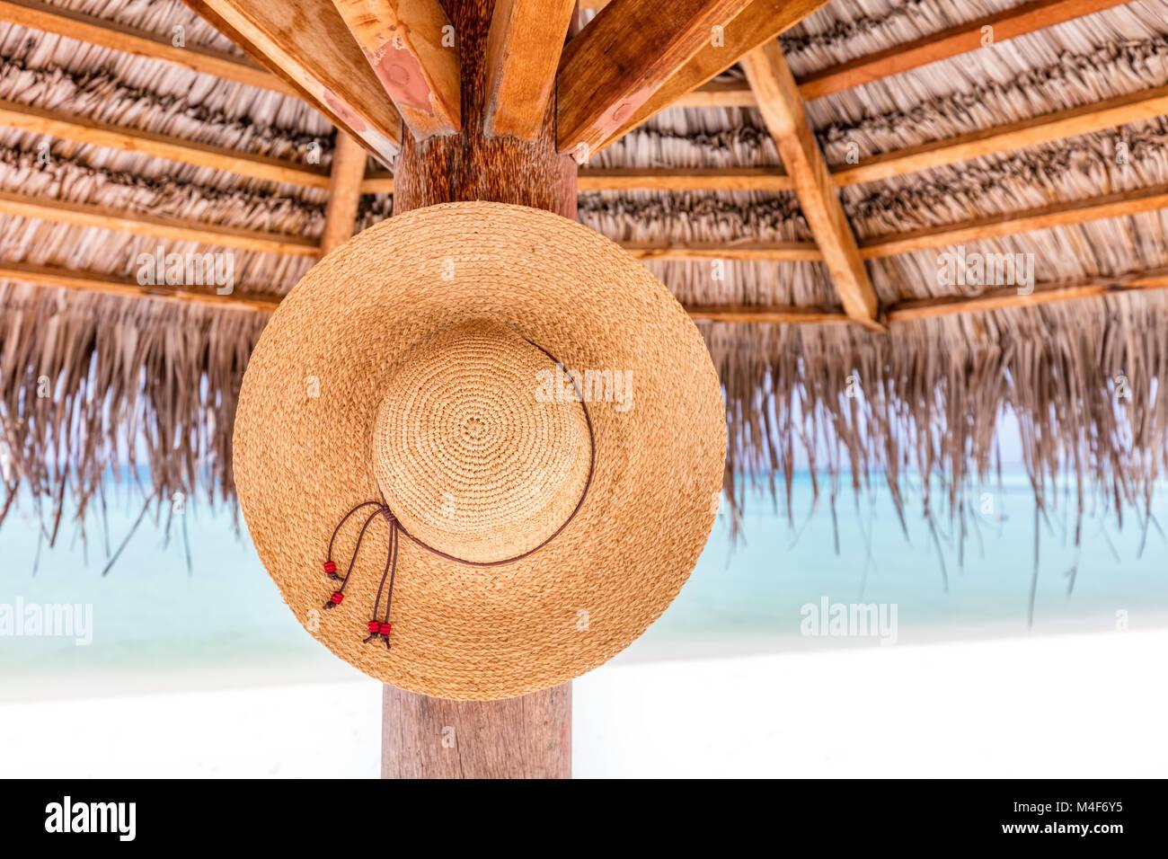 b30ca430499 Sun hat hanging on sunshade umbrella on tropical beach. Maldives ...