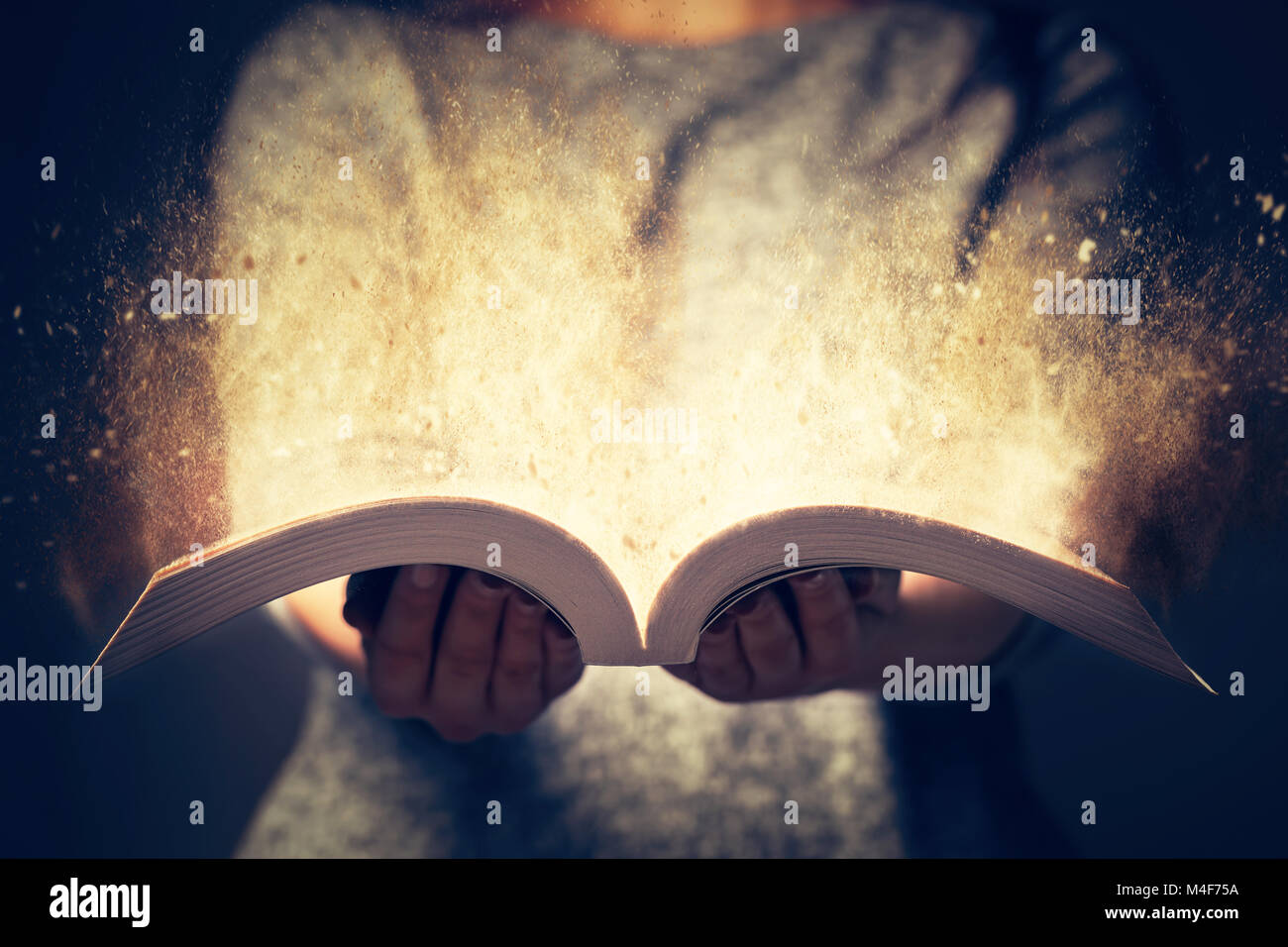 Woman holding an open book bursting with light. - Stock Image