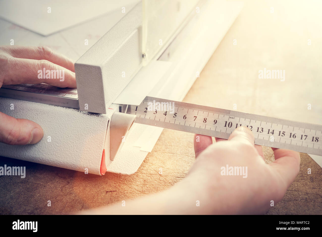 Man does measuring with slide calliper in paper cutter - Stock Image