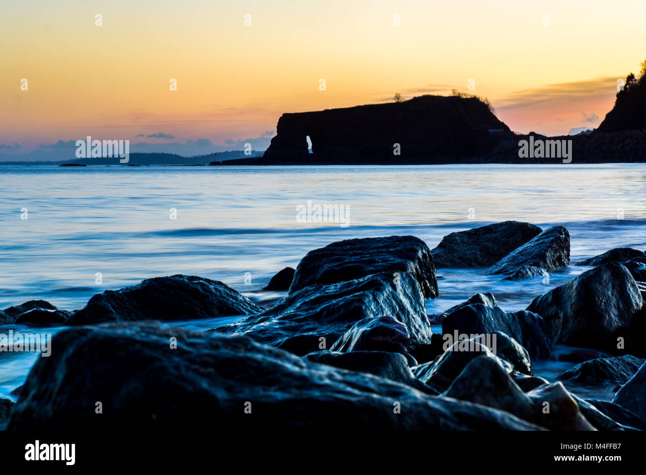 A landscape image of the rocks on the sea front, in the background is the famous red rock of Dawlish Warren, Devon, - Stock Image