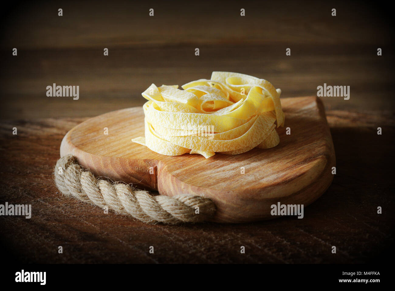 Nest of pasta tagliatelle on wooden cutting board aon rustic background. Selective focus - Stock Image