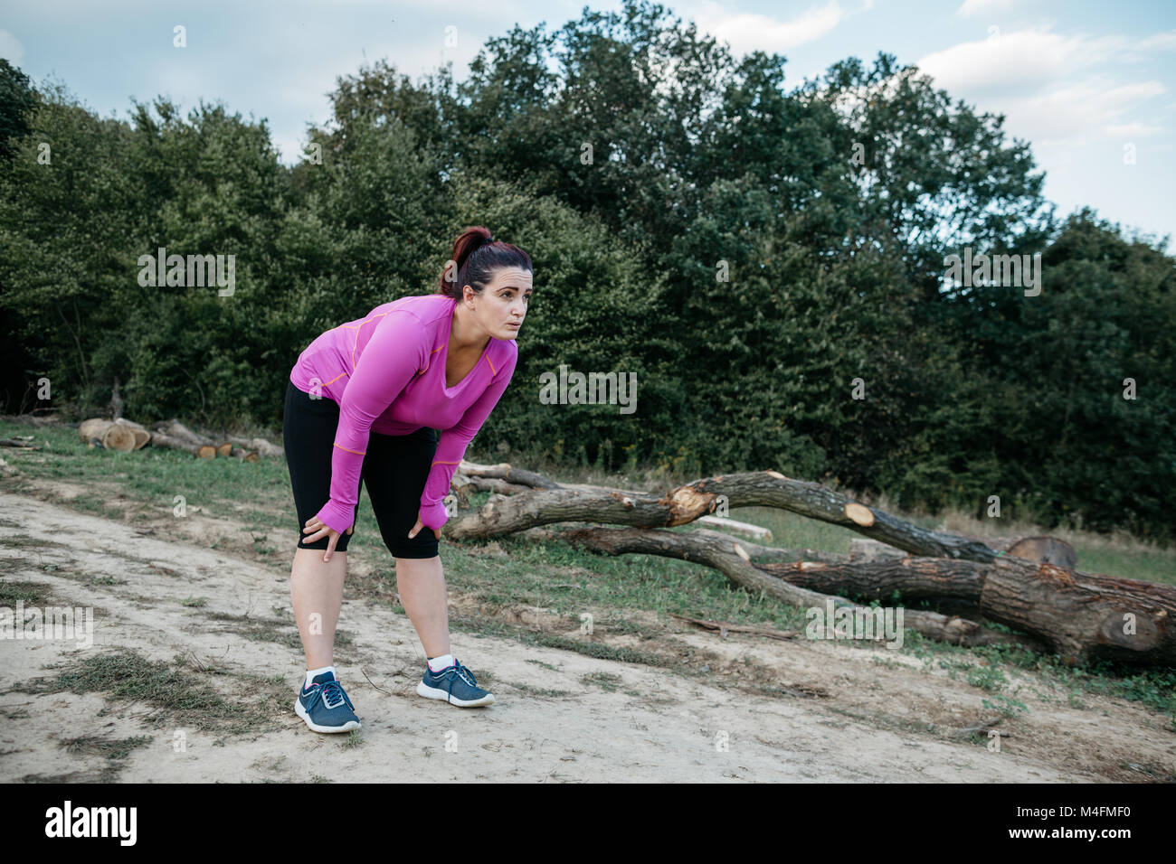 Portrait of a plus size female runner bending over and resting. - Stock Image
