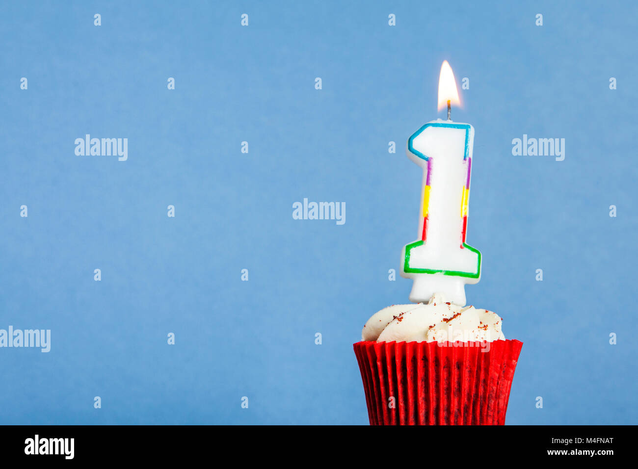 Number 1 Birthday Candle In A Cupcake Against Blue Background