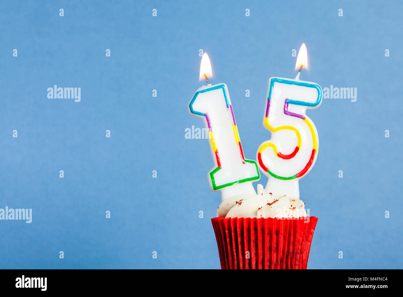 Number 15 Birthday Candle In A Cupcake Against Blue Background