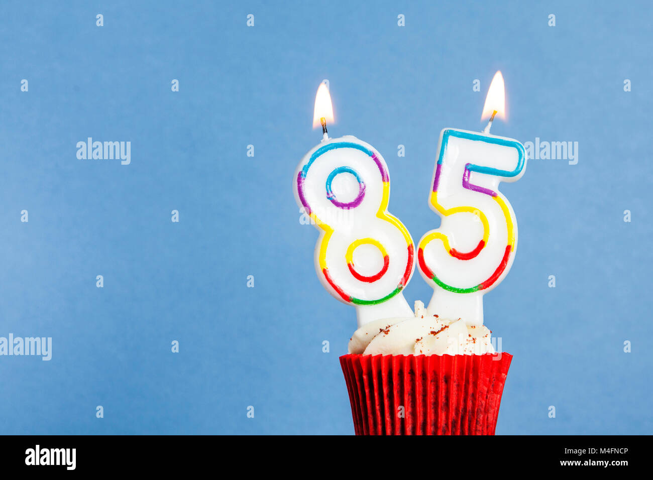 Number 85 Birthday Candle In A Cupcake Against Blue Background