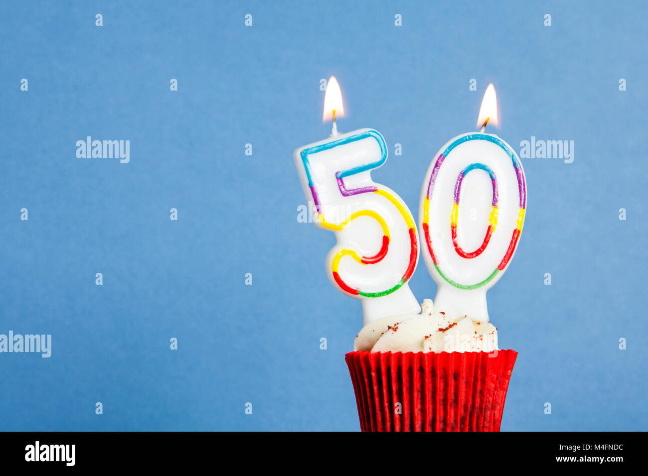 Number 50 Birthday Candle In A Cupcake Against Blue Background