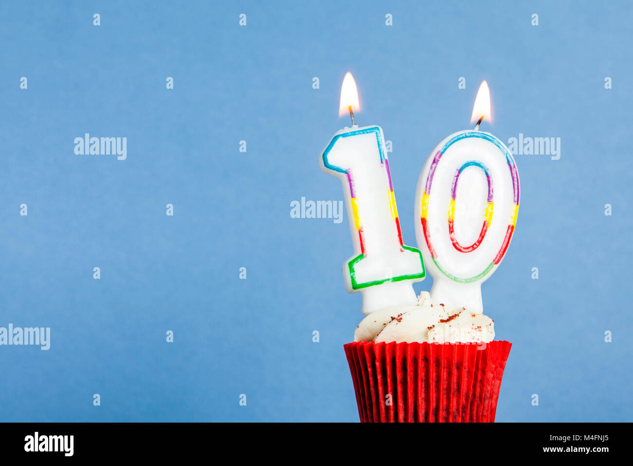 Number 10 birthday candle in a cupcake against a blue background - Stock Image