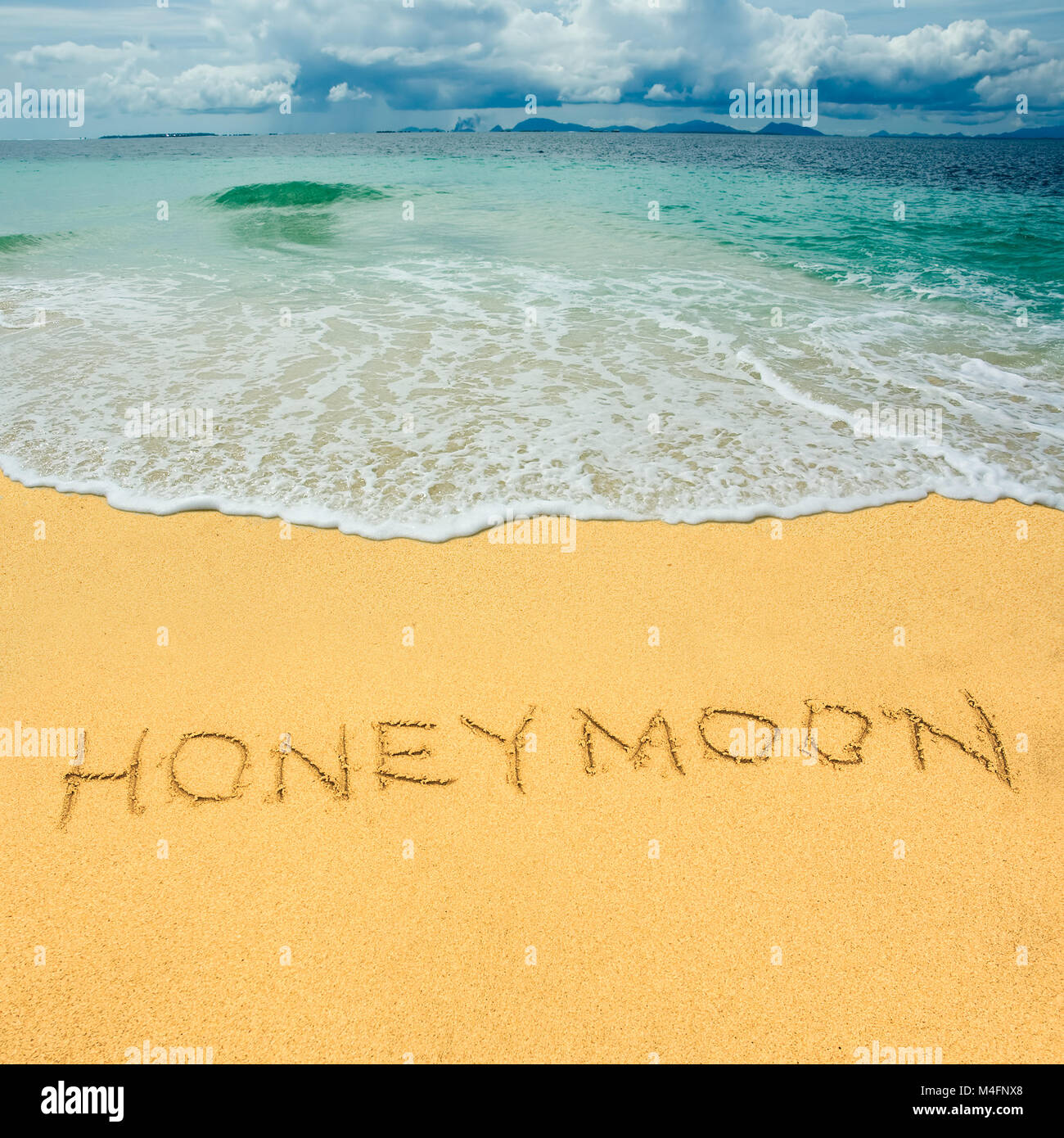 Honeymoon drawn in a sandy tropical beach - Stock Image