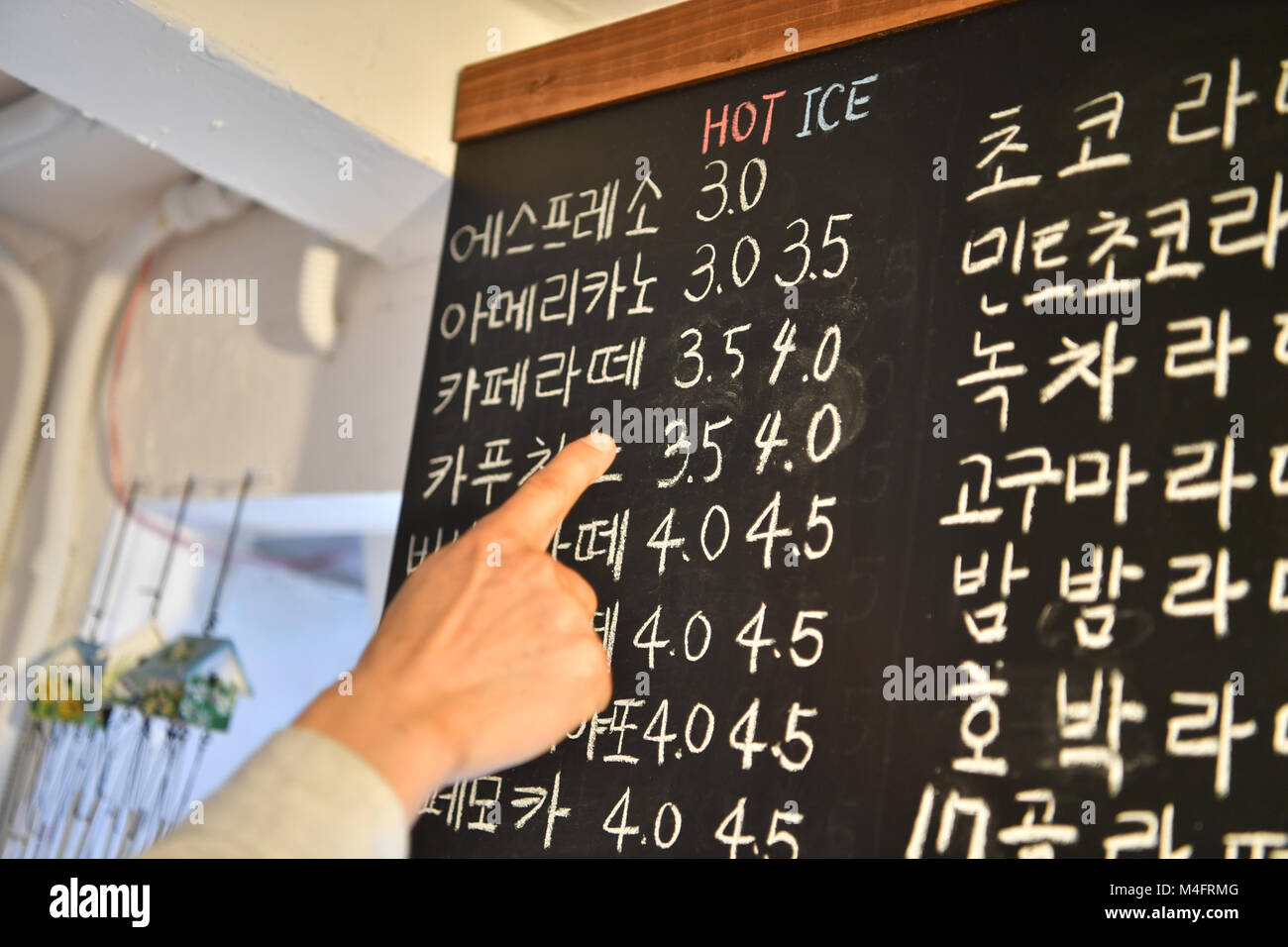 Gangneung, South Korea. 16th Feb, 2018. A finger pointing at the price for a white coffee on a price baord in Korean - Stock Image