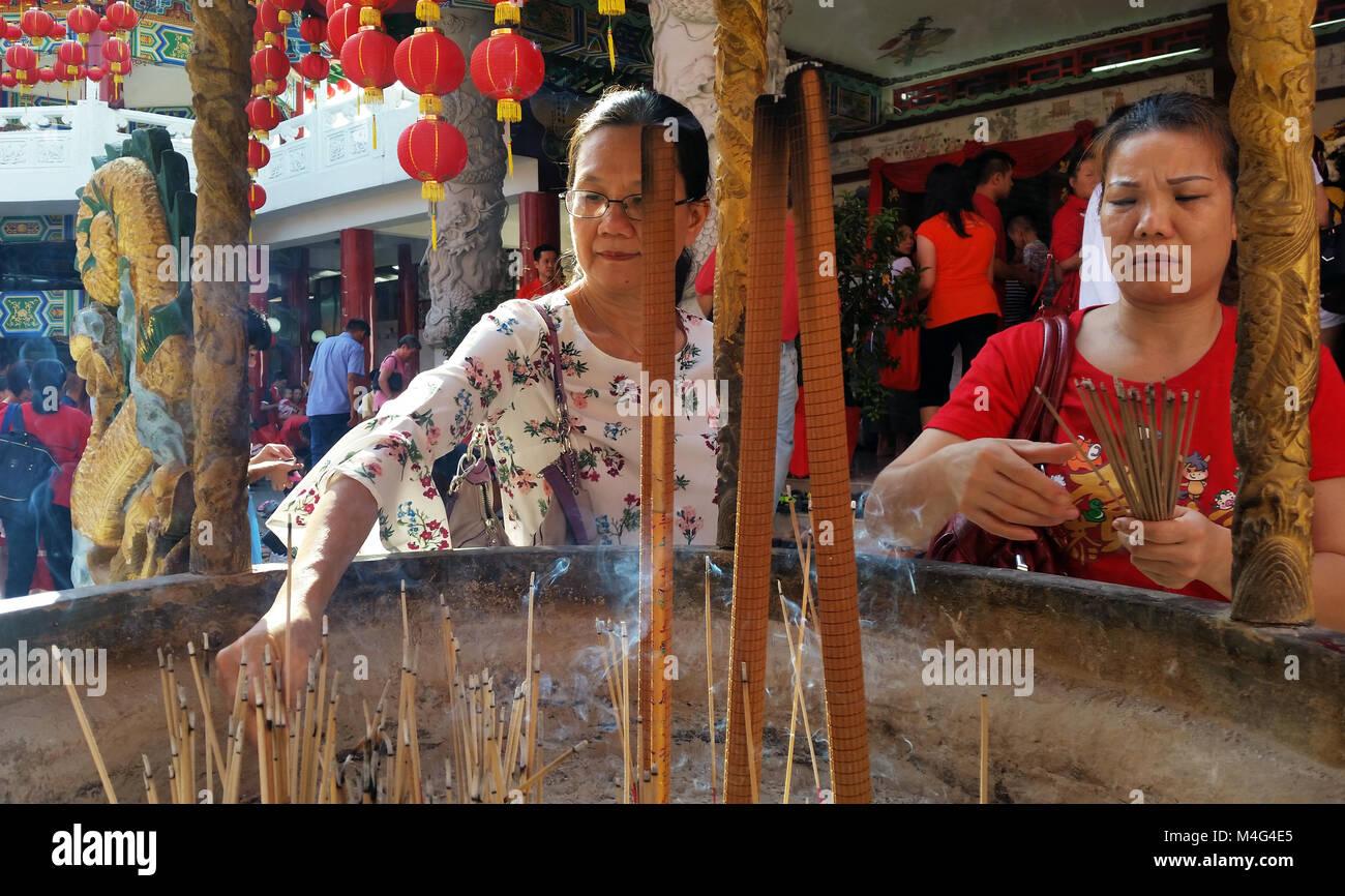 Kuala Lumpur, Malaysia - February 16, 2018: Women burn incense