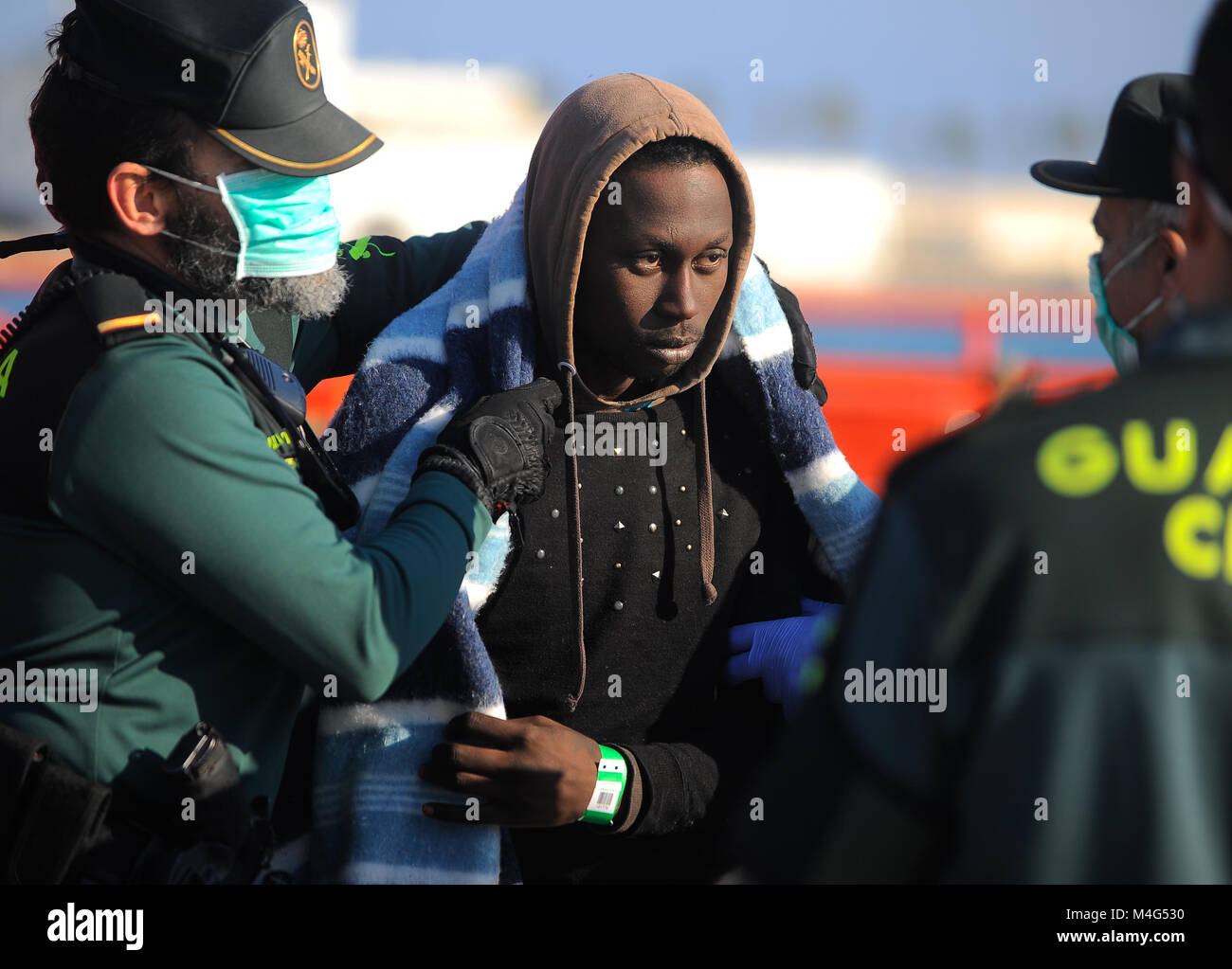 Malaga, Malaga, Spain. 16th Feb, 2018. A migrant is being led by member of Civil Guard. Arrival of a group of migrants Stock Photo