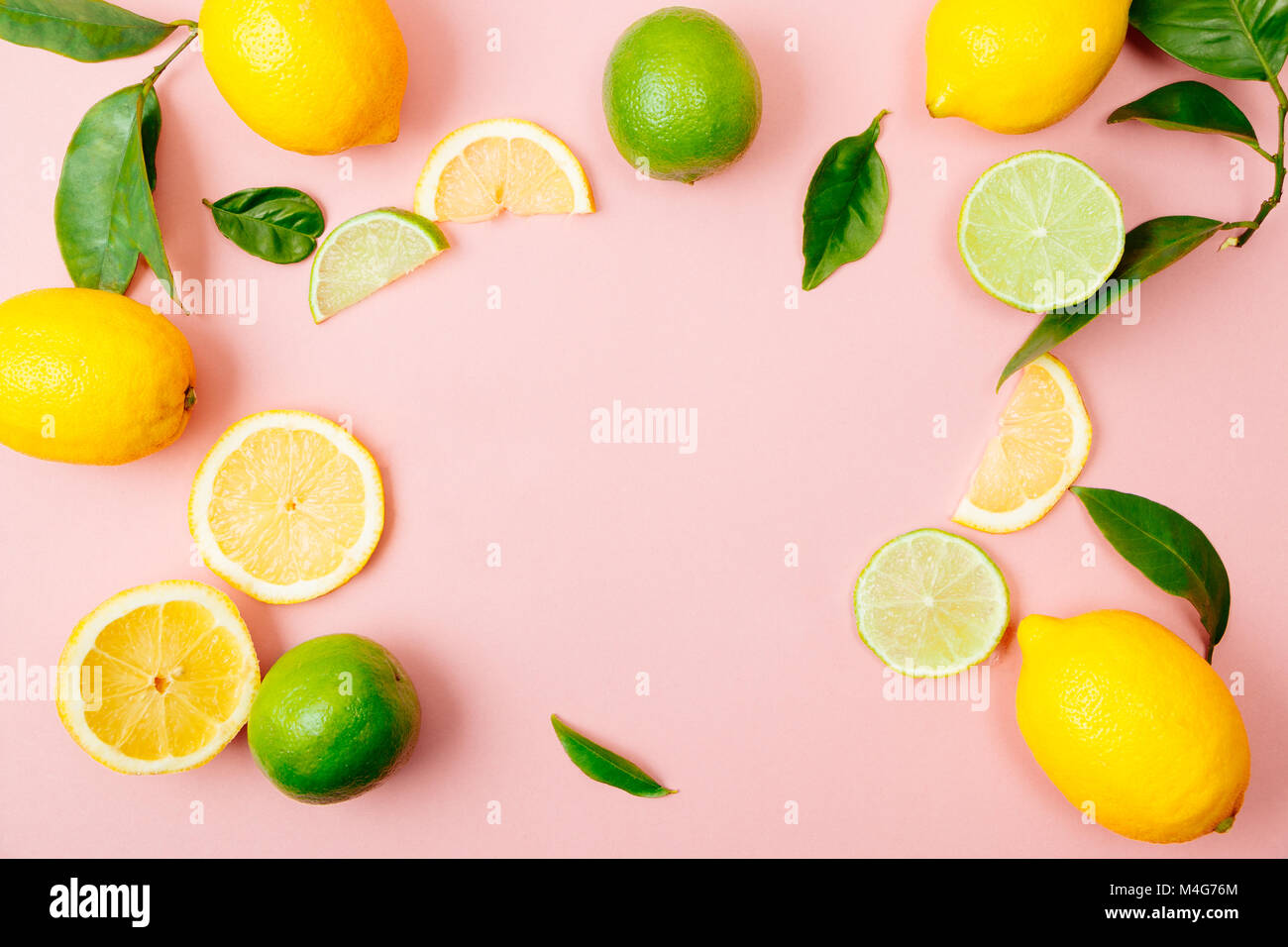 Flat lay of citrus fruits like lime and lemon with lemon tree leaves on light pink background making a frame - Stock Image
