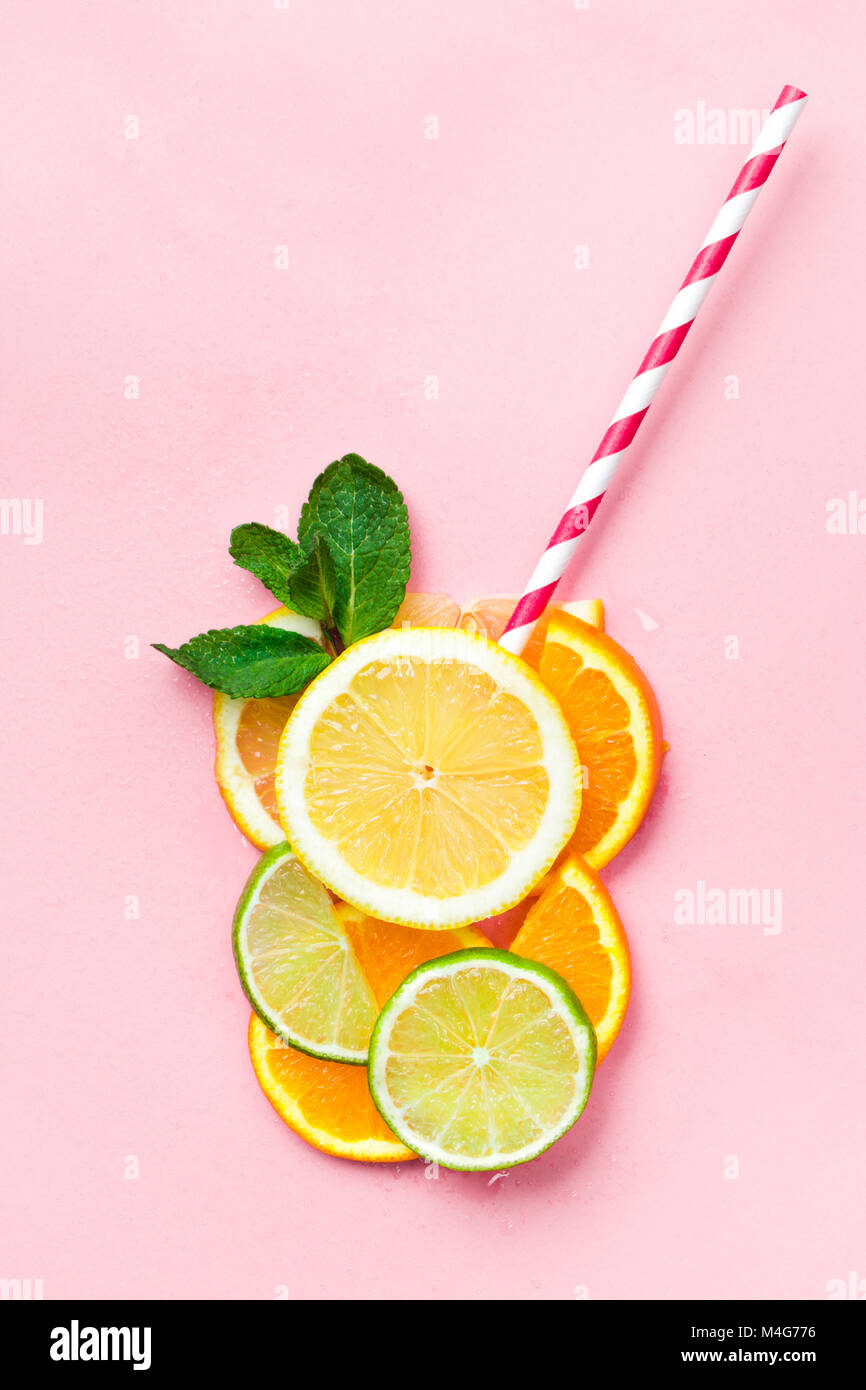 Glass of juice made of citrus slices with mint leaves and a straw on light pink background. Citrus juice concept - Stock Image