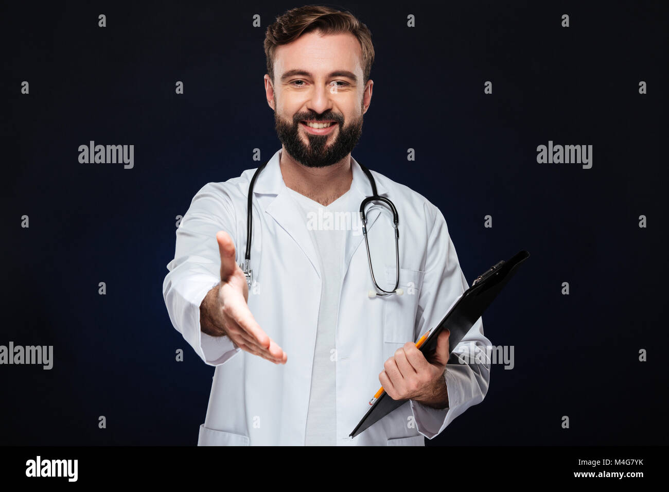 Portrait of a happy male doctor dressed in uniform with stethoscope standing with outstretched hand for greeting Stock Photo