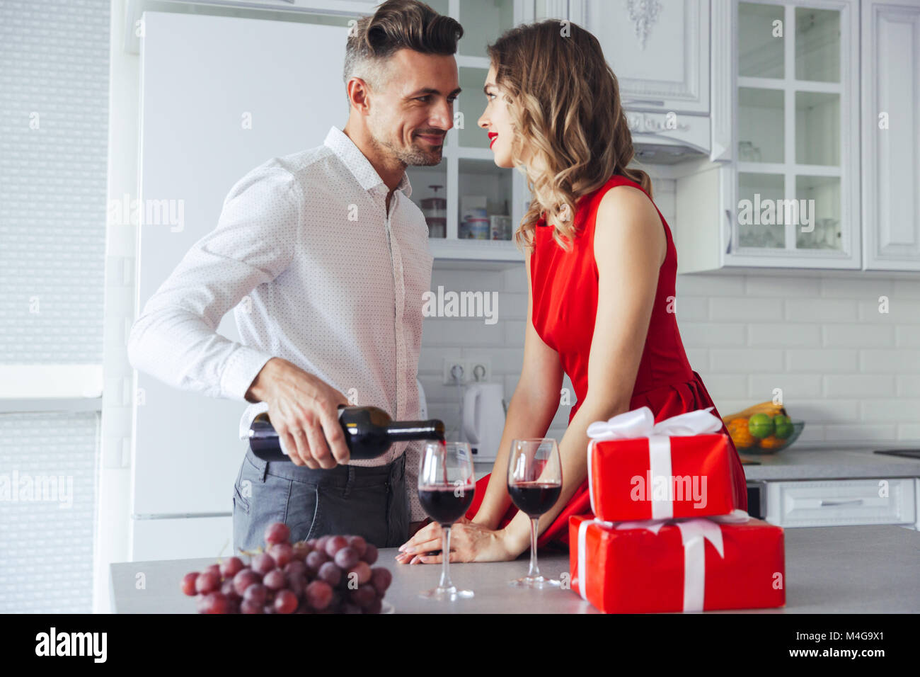 Young man in white shirt pouring wine into glasses and looking at his gorgeous woman in red dress on valentines - Stock Image