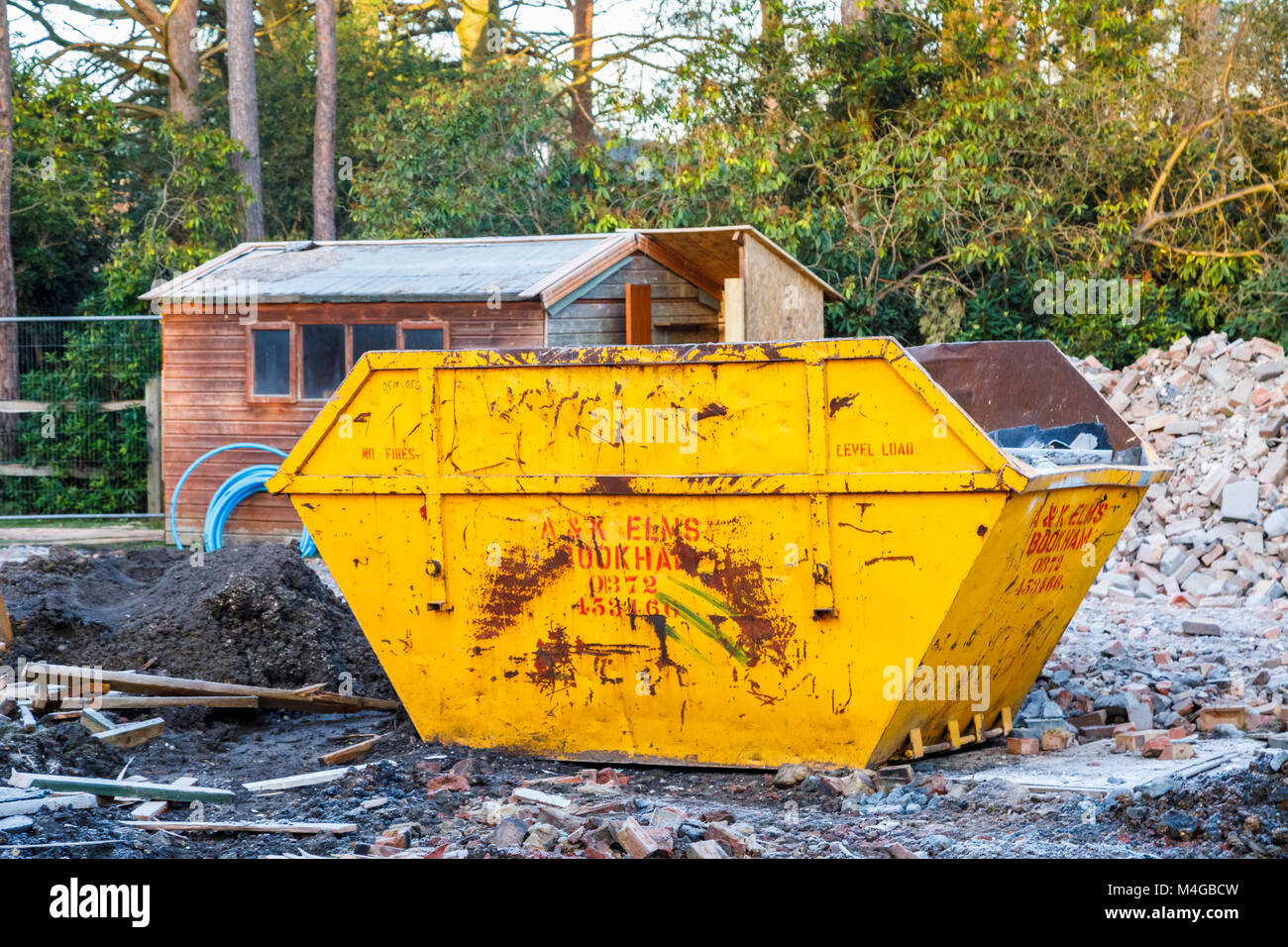 Real estate construction site: yellow skip in the remains of the demolition of a residential house property on a - Stock Image