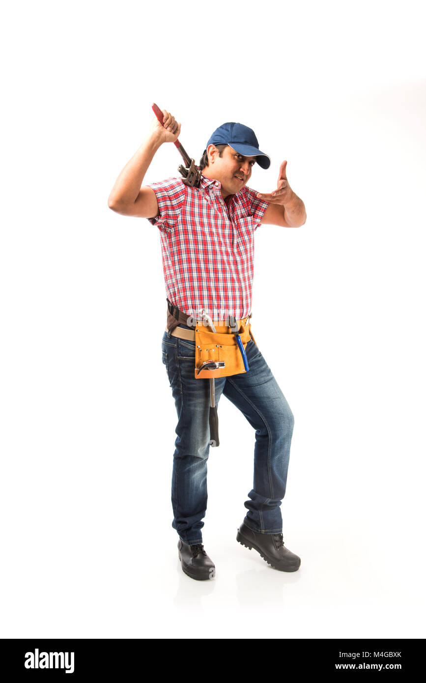 Indian plumber posing with Pipe wrench or plumbing spanner, standing ...