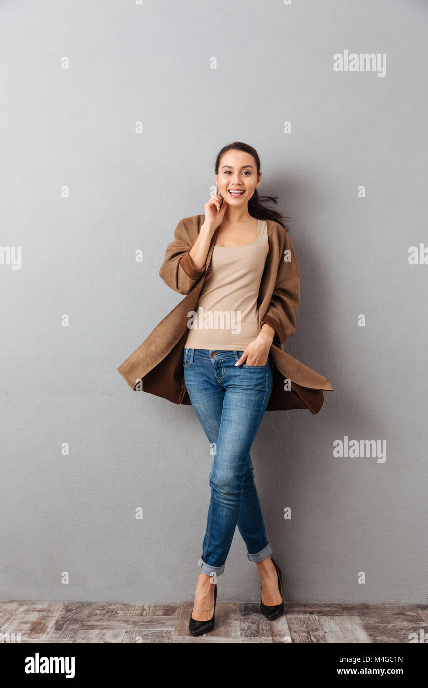 Full length of a smiling young asian woman whirling around over gray background - Stock Image