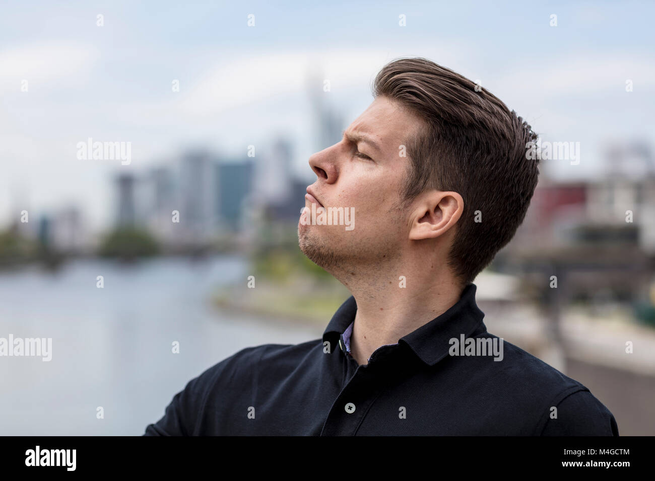 Profile of an angry man with city skyline in the background. - Stock Image