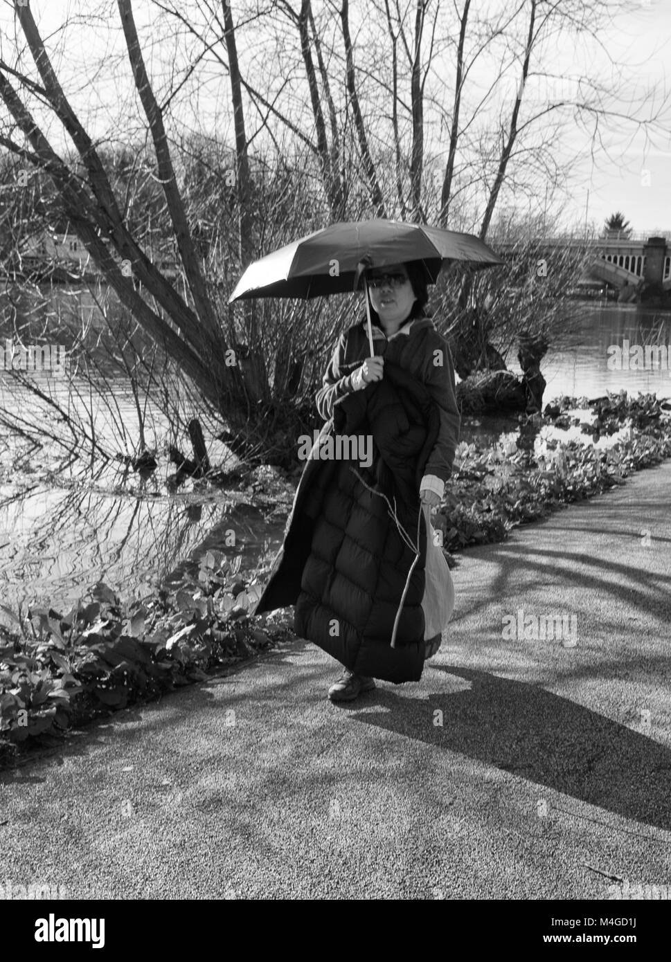 Black & White Photograph of a woman taking a stroll by the river thames, Richmond, London, England, UK. Credit: - Stock Image