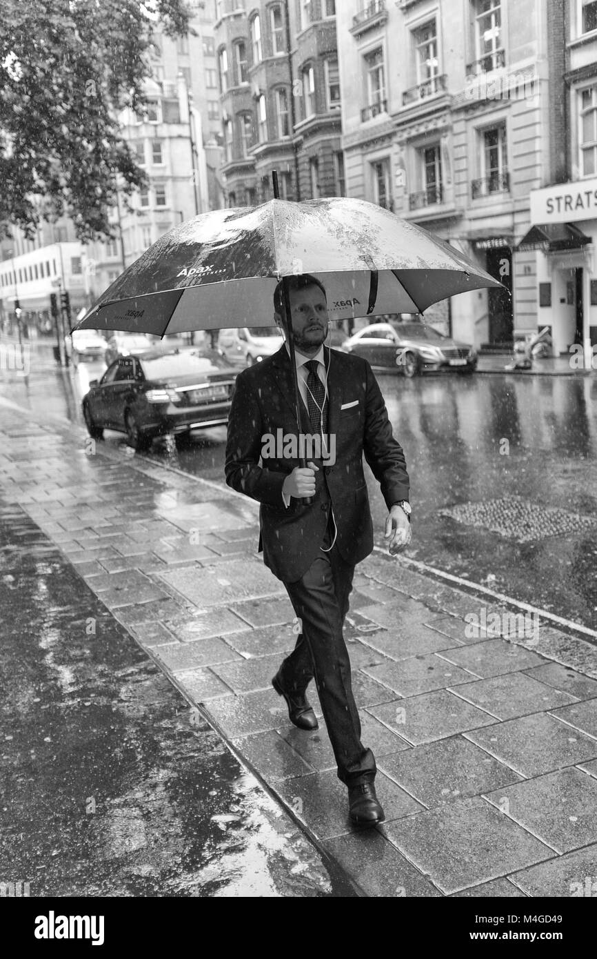 Black & White Photograph of a man holding his umbrella in a wet Mayfair, London, England, UK. Credit: London - Stock Image