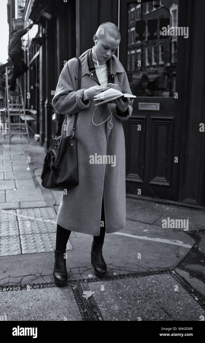 Black & White Photograph of a woman multi-tasking in Fitzrovia, London, England, UK Credit: London Snapper - Stock Image