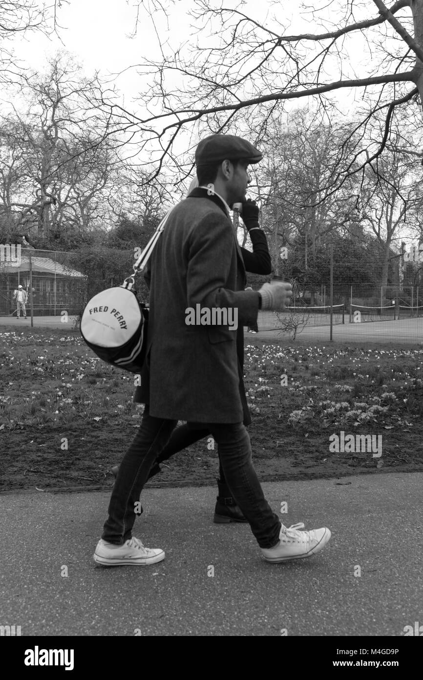 Black & White Photograph of a man with a Fred Perry Bag in Lincoln's Inn Fields, Holborn, London, England, - Stock Image