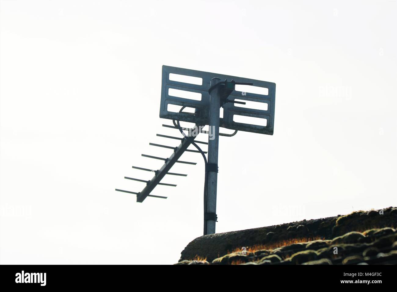 TV aerial on gable end of a moss covered tiled roof - Stock Image