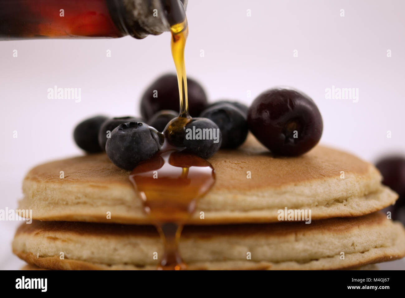 Breakfast pancakes with blueberries, cherries and maple syrup isolated on a white background with very shallow depth - Stock Image