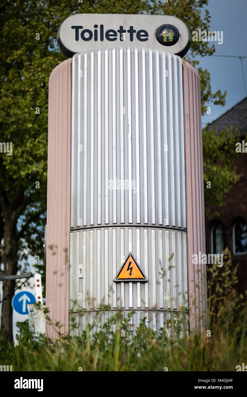 Public toilette on the street with high voltage signs in daytime, in Germany, Europe, shot 2017 - Stock Image