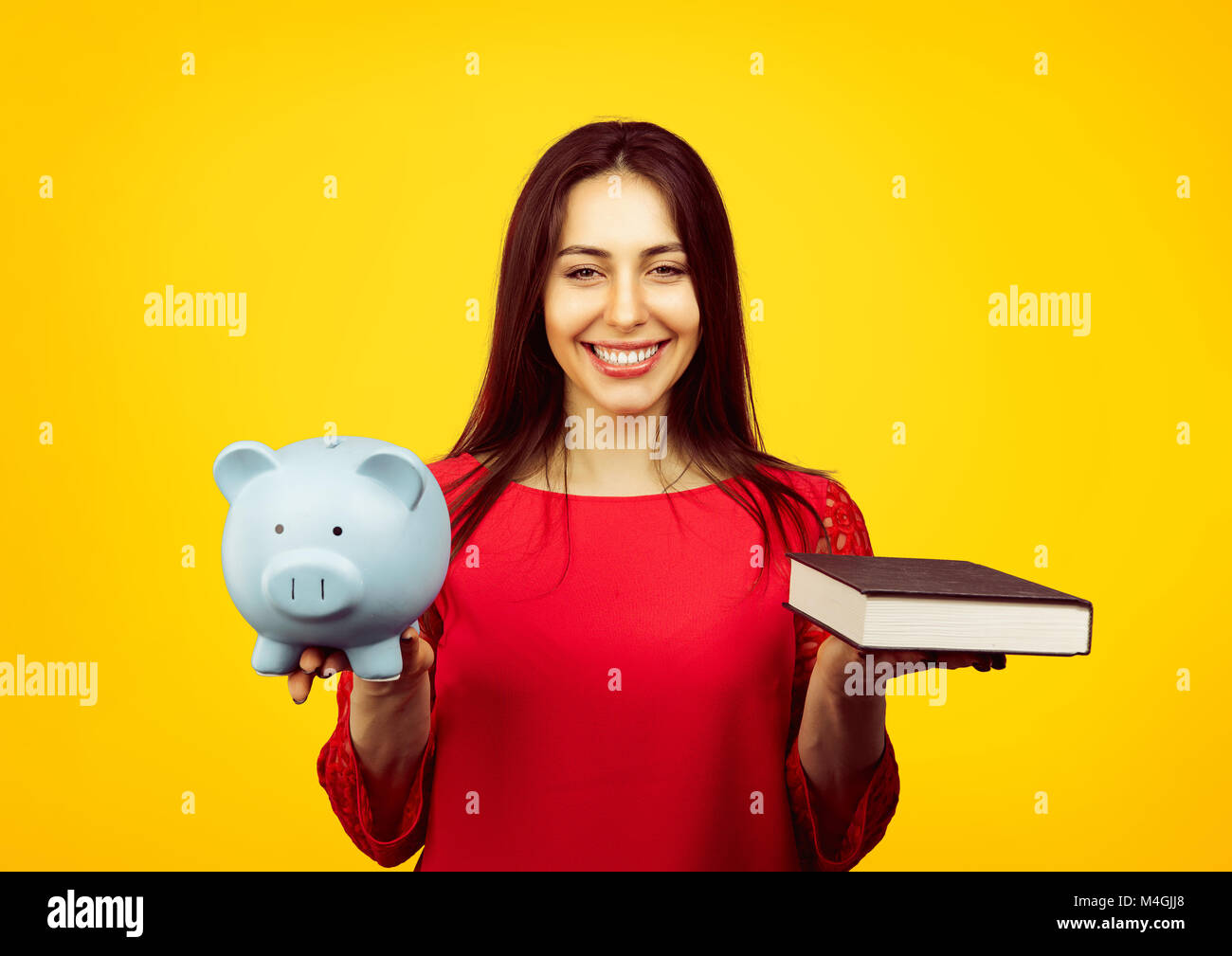 Content female student showing book and piggy bank content with savings and scholarship isolated on yellow background - Stock Image