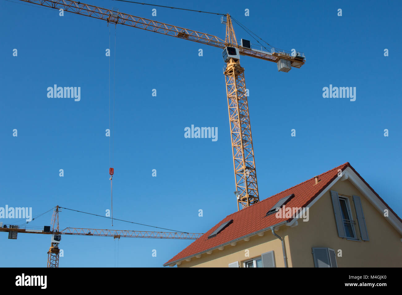 Yellow eracted crane over a red roof constructed facility in bluw sky at daylight, shot 2017 - Stock Image