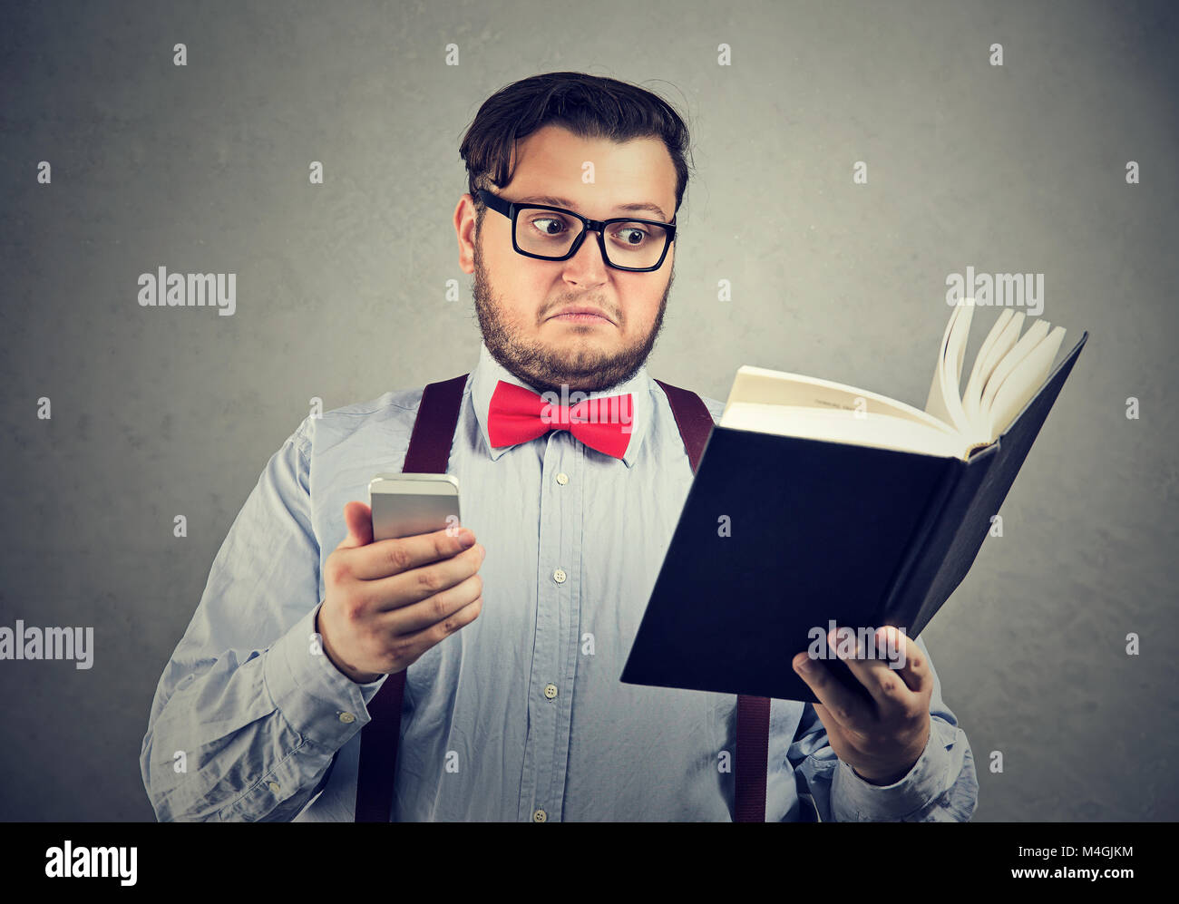 Young chubby man holding printed book and smartphone looking extremely puzzled. - Stock Image