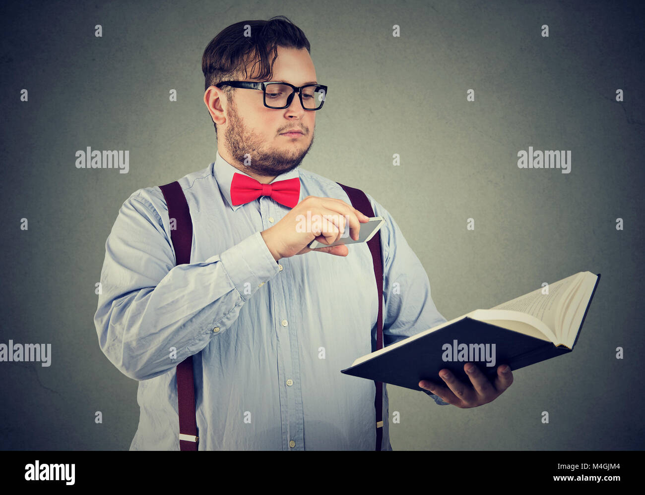 Smart man in eyeglasses holding and taking photo of precious information with smartphone. - Stock Image