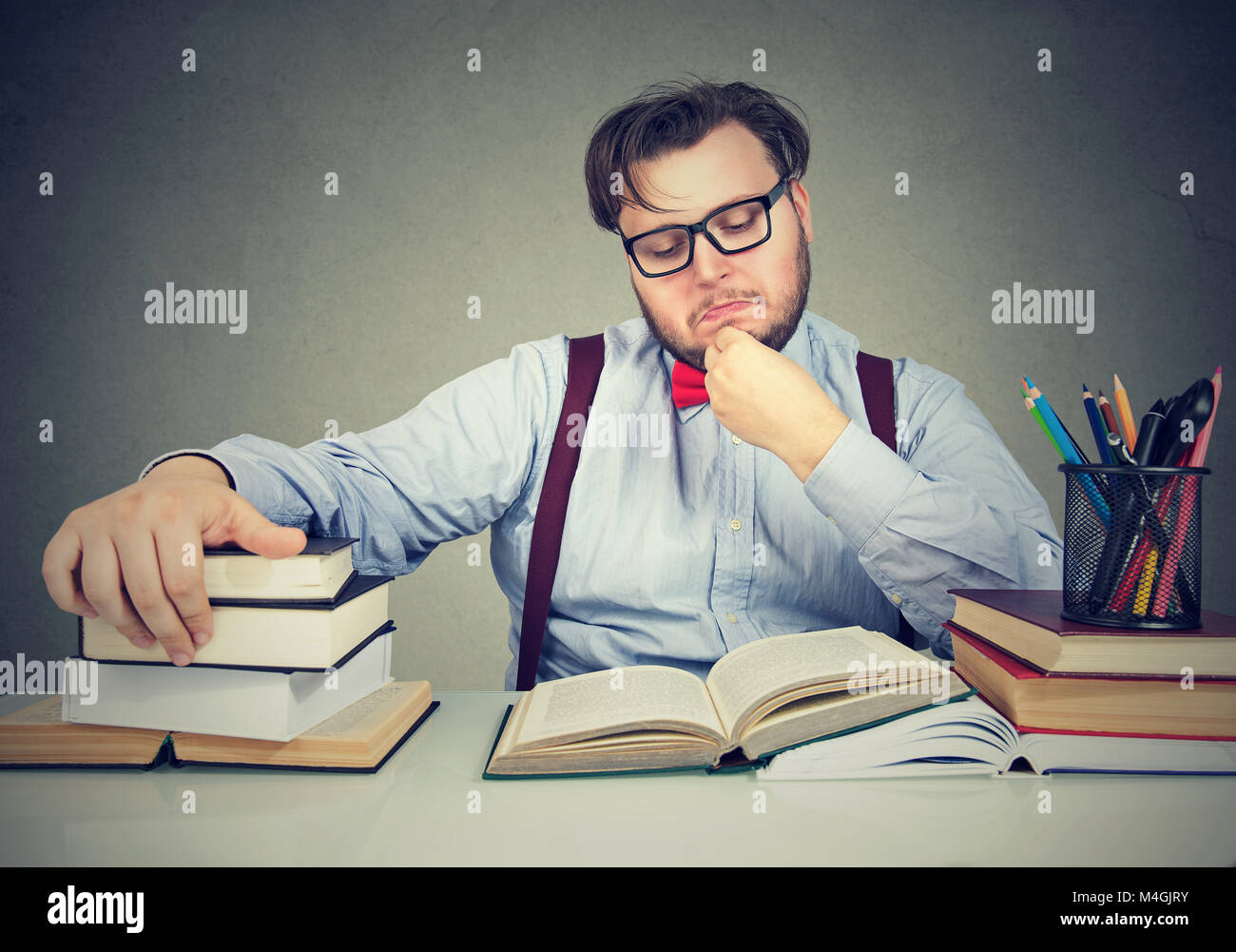 Young chunky man sitting at desk and reading books - Stock Image