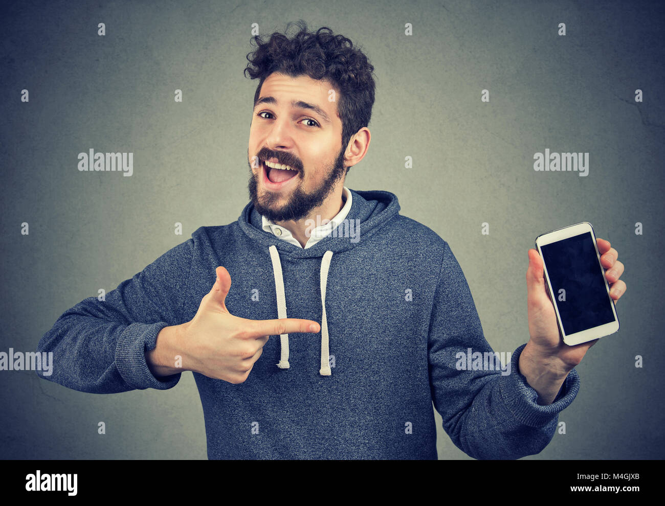 Young cheerful man showing new phone happy with great quality. - Stock Image