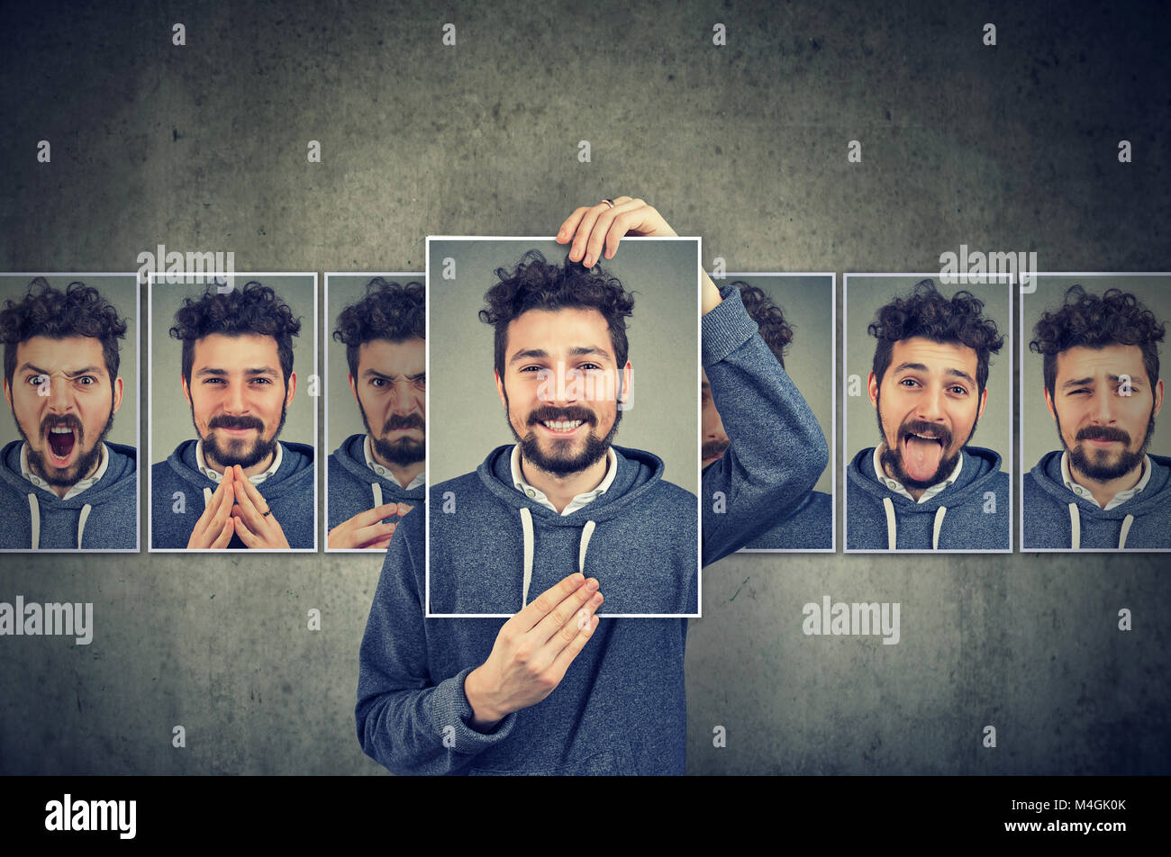 Positive masked young man in glasses expressing different emotions - Stock Image