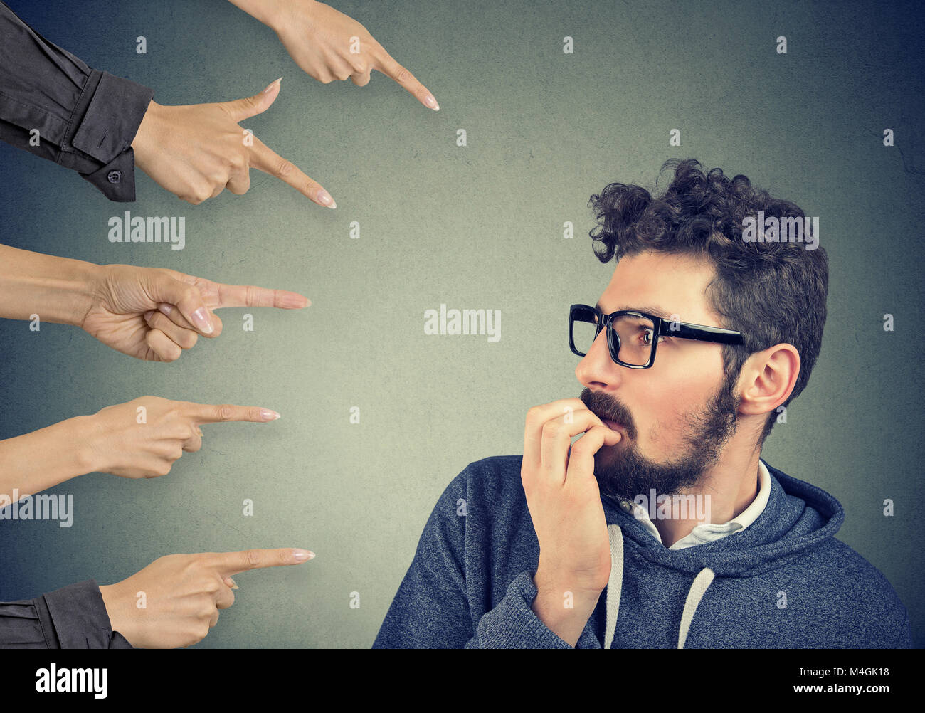 Anxious man judged by different hands. Concept of accusation of guilty guy. Negative human emotions face expression - Stock Image
