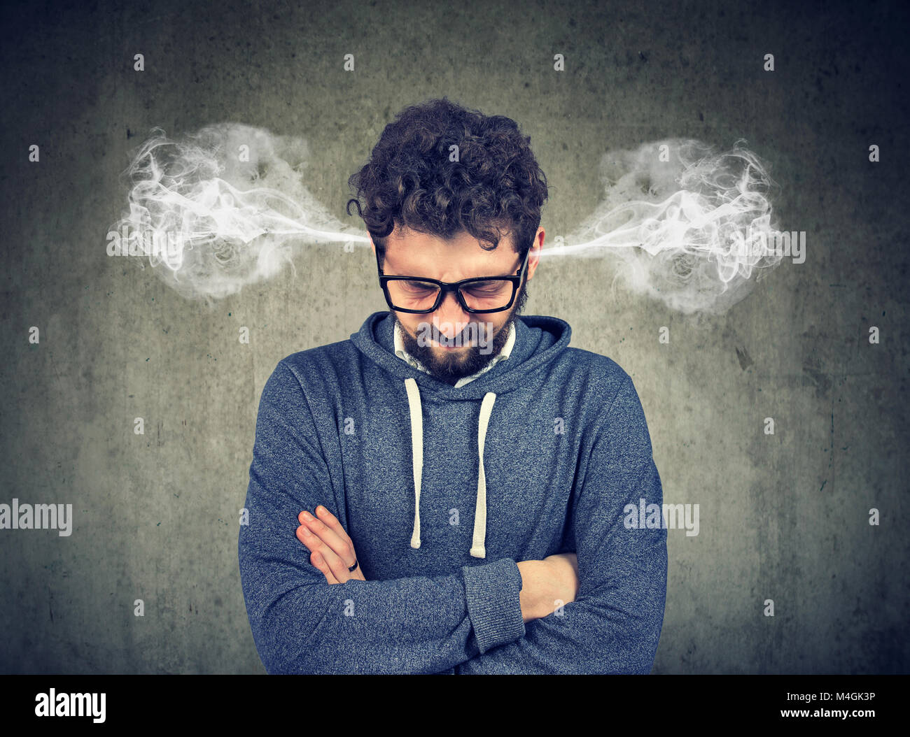 Angry young man, blowing steam coming out of ears, about to have nervous breakdown isolated on gray background. - Stock Image