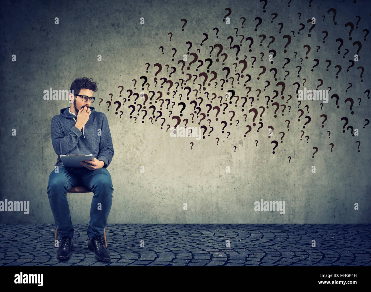 Anxious man sitting with resume anticipating interview, having plenty of questions and looking scared. - Stock Image